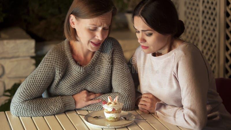 Femelle deux affamée regardant le dessert doux en café, casse-croûte malsain, calories photographie stock libre de droits