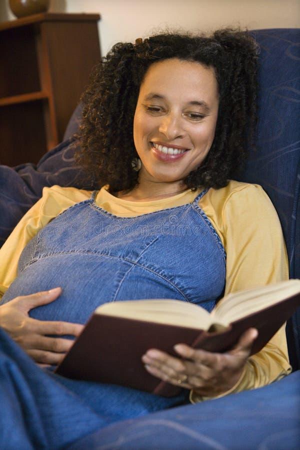 Femelle enceinte affichant un livre photographie stock