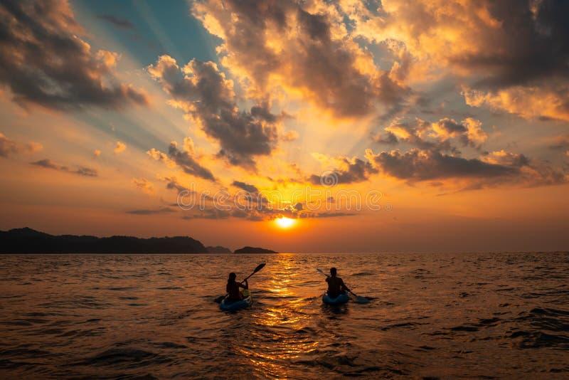 Femelle et une navigation masculine avec des canoës près de l'un l'autre au coucher du soleil photographie stock
