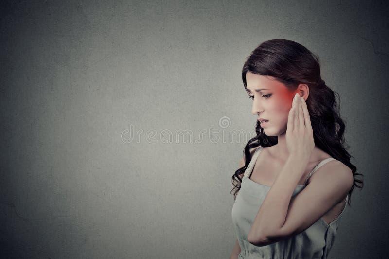 Femelle malade ayant la douleur aux oreilles touchant son temple principal douloureux coloré en rouge photo stock