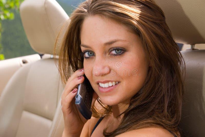 Femelle parlant sur le téléphone portable dans le véhicule photographie stock libre de droits