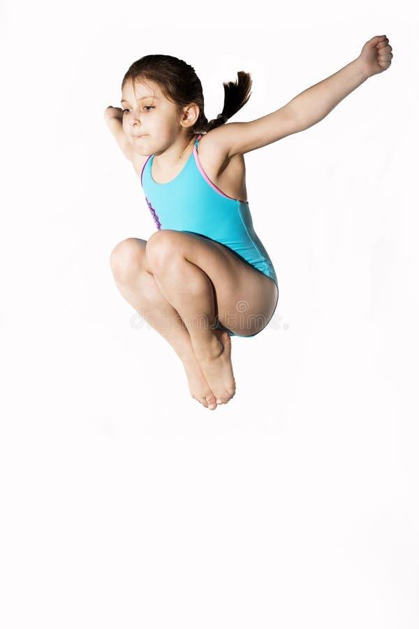 Femelle peu caucasienne 7 années de fille dans le costume de natation cyan sautant sur le fond blanc photographie stock libre de droits