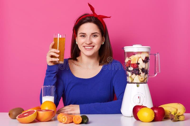 Femelle sincère de sourire utilisant le pull molletonné bleu et le bandeau rouge, tenant le verre avec le mélange utile nutrit photos stock