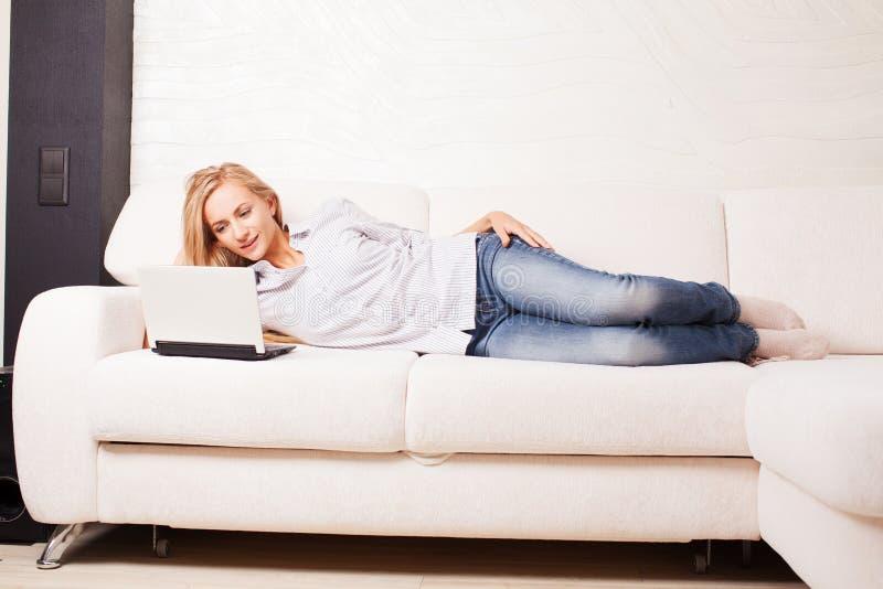Femelle sur le sofa avec l'ordinateur portable photo stock