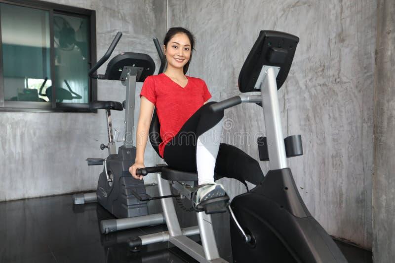 Femelle sur le vélo de gymnase faisant le cardio- exercice images stock