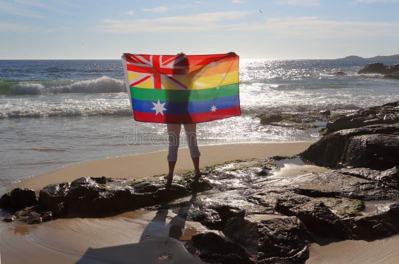 Femelle tenant un drapeau australien dans des couleurs d'arc-en-ciel photos stock