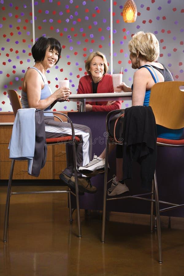 Femelles adultes s'asseyant à la table dans le club de santé. photos libres de droits