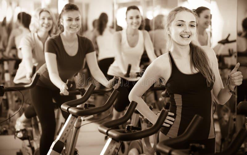 Femelles faisant un cycle dans le club de sport photo libre de droits