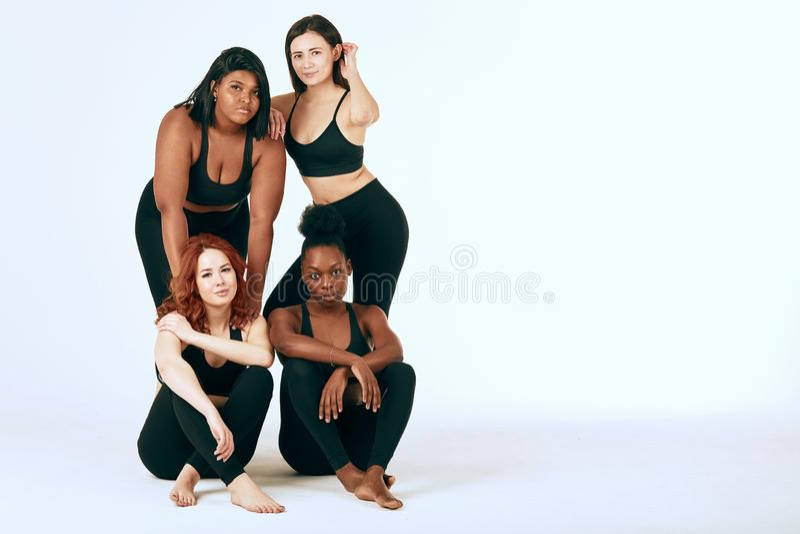 Femelles multiraciales avec le support diff?rent de taille et d'appartenance ethnique ensemble et le sourire photo stock