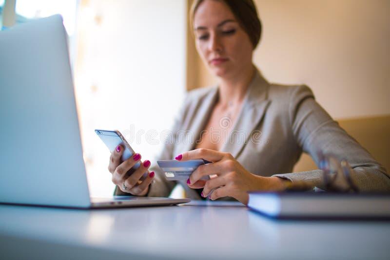 Femenino haciendo en línea ordenar vía el teléfono móvil imagen de archivo