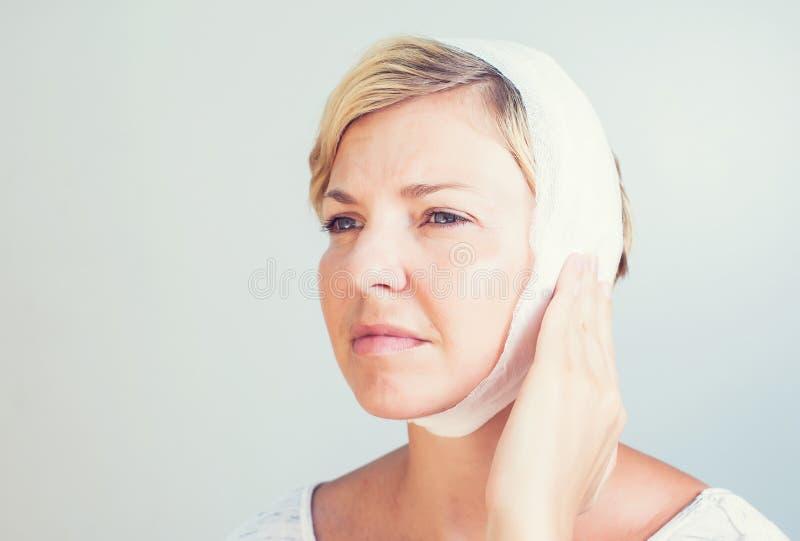 Femenino joven teniendo dolor de oído que toca su dolor de oídos principal doloroso imagen de archivo