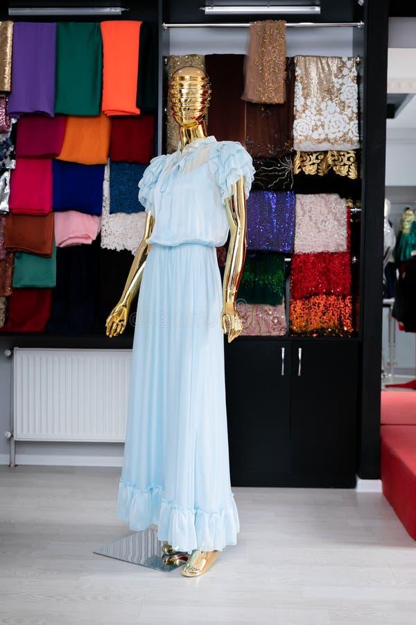 Femenino, largo, Tulle, azul clara, vestido en un maniquí de oro foto de archivo
