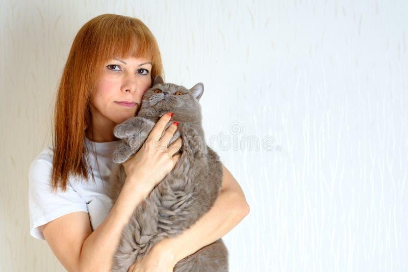 Femenino mayor maduro del pelo rubio o rojo relajando en casa el gato de ronroneo lindo que se sostiene y huging fotos de archivo