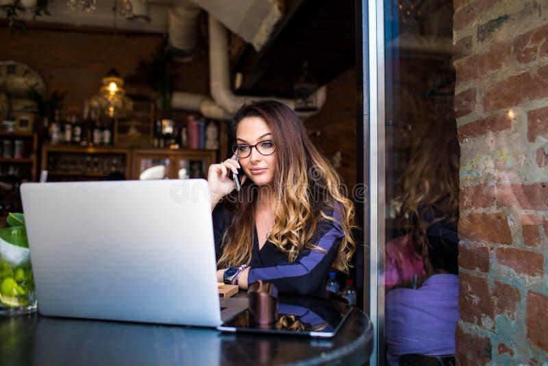 Femenino teniendo conversación del teléfono móvil durante resto en café imágenes de archivo libres de regalías