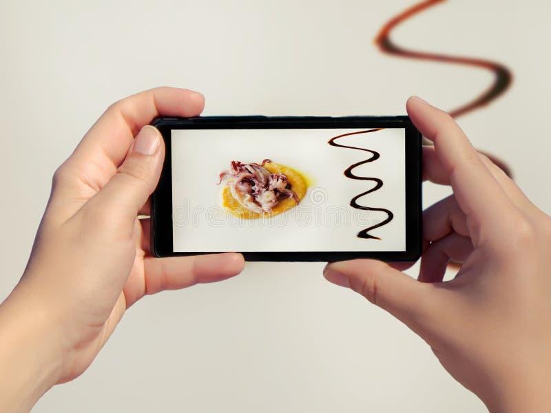 Femenino tome la imagen de la comida de alta calidad en un restaurante en el fondo blanco en el teléfono móvil El cocinar de alta imágenes de archivo libres de regalías