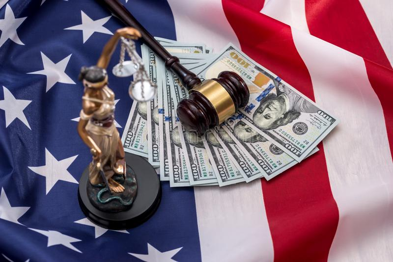 femida, dólar, mazo y bandera imagen de archivo