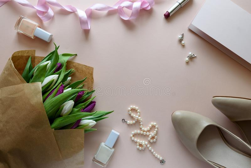 Feminine accessories, bouquet of white and purple tulips and blank paper on pink background. Top view. Flat lay. Copy space. stock images