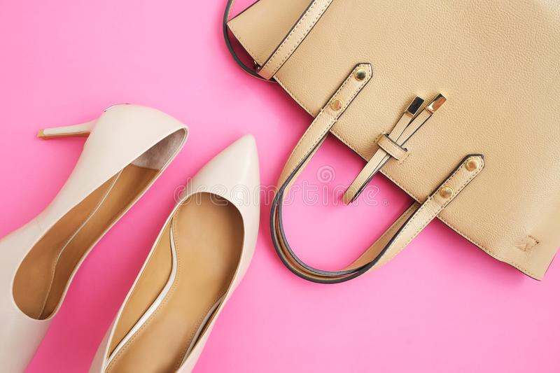 Feminine accessories flat lay. Woman shoes and bag on pink background. Beige color woman accessories. Text space. Top view. royalty free stock images