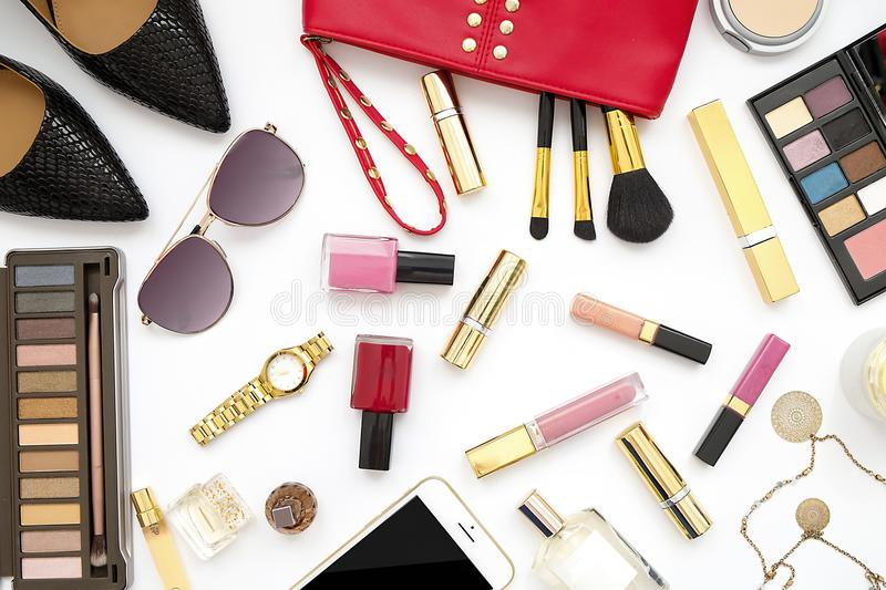 Flat lay feminine accessories collage with beige high heel shoes, sunglasses and cosmetics set on white background. Text space. Be stock photos