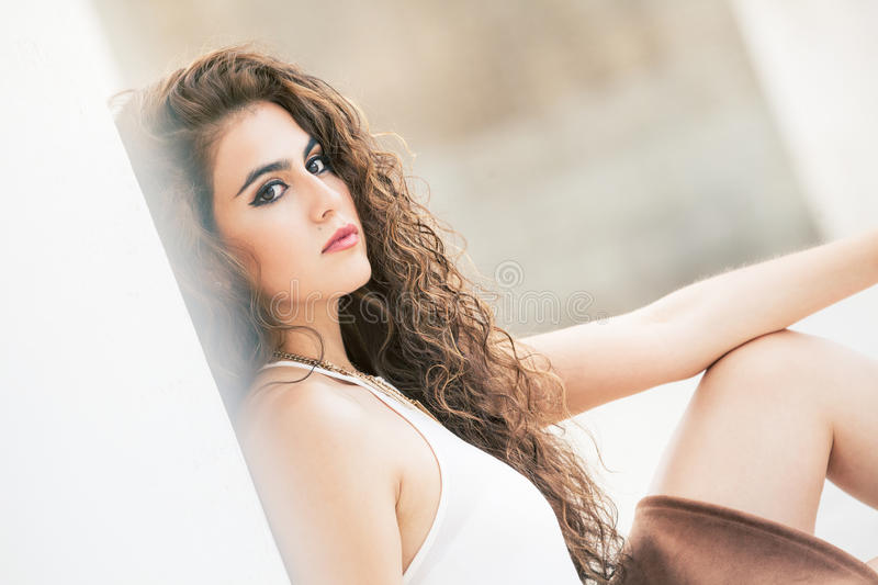 Feminine beauty. Curly-haired young woman model. stock photo
