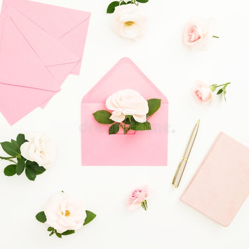 Feminine composition with roses flowers, paper cards and notebook on white background. Valentines day. Flat lay, top view stock image