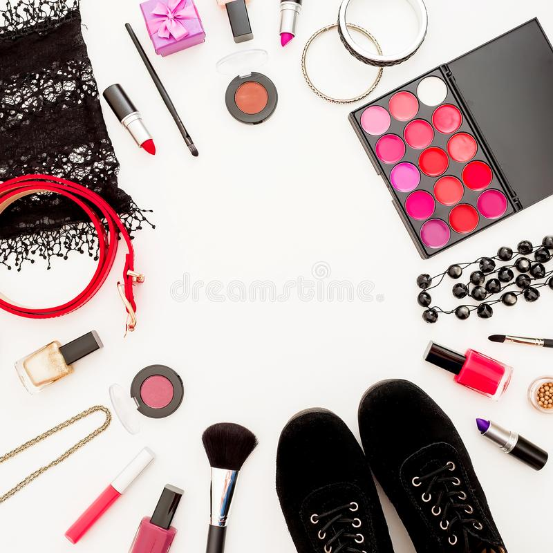 Feminine desk with cosmetics, accessories and shoes on white background. Flat lay, top view. royalty free stock photography