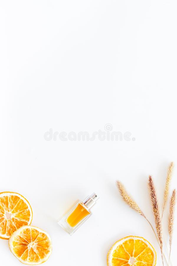Feminine desk with perfume bottle, flowers and dry oranges on white background top view copy space. Feminine desk with perfume bottle, flowers and dry oranges on stock image