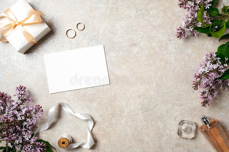 Feminine desk with wedding accessories, blank paper card, rings and spring lilac flowers. Wedding concept, invitation card mock up royalty free stock images