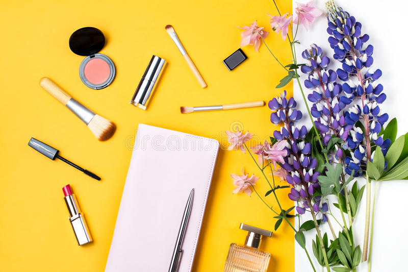 Feminine desk workspace with diary, makeup products, flowers, perfume royalty free stock photo
