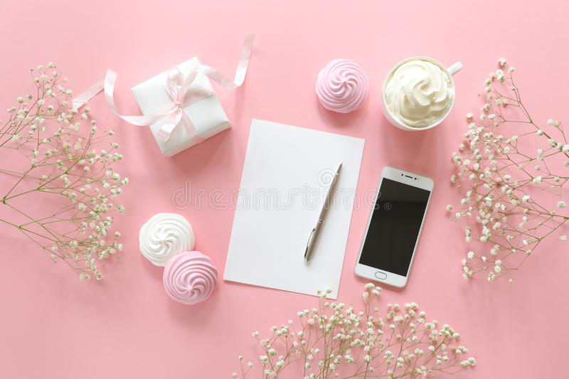 Feminine desk workspace in white and pink colors with small baby`s-breath flowers gypsophila. royalty free stock photo