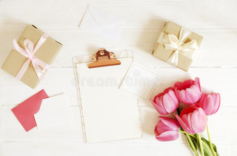 Feminine desktop composition with blank greeting card sheet clipboard, envelope, pink tulips bouquet, craft paper present wrap on royalty free stock images