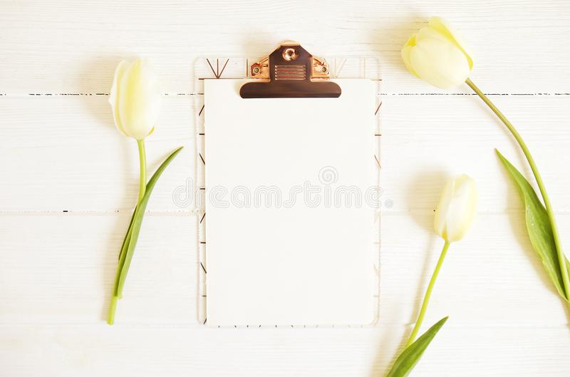 Feminine desktop composition with blank sheet clipboard & white tulips on wooden texture table background, copy space for text. Wo stock images