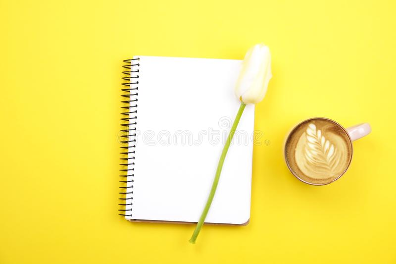 Feminine desktop composition with blank sheet notebook, coffee cup latte art, tulips bouquet on yellow background. Girlie workplac stock photo
