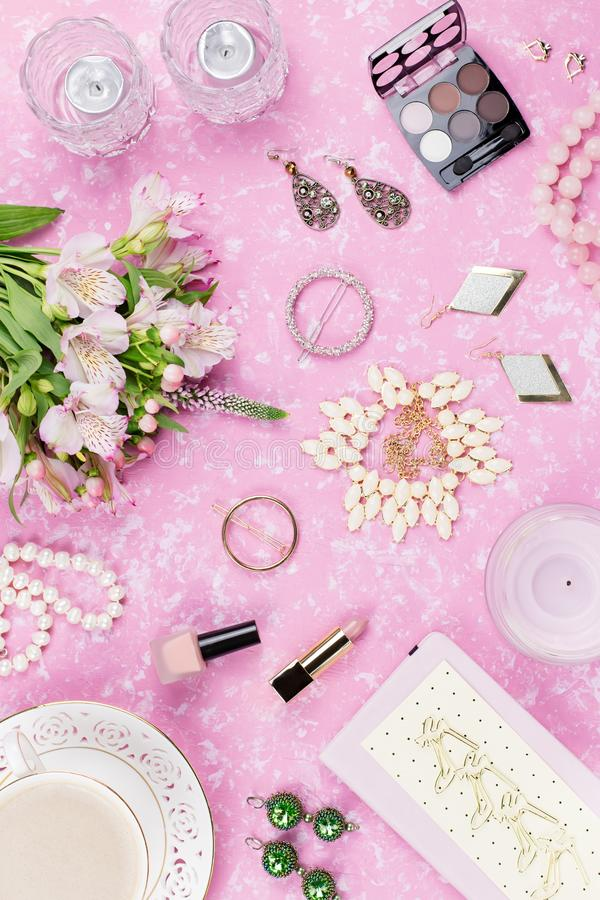 Feminine flat lay with woman fashion accessories, jewelry, cosmetics, coffee and flowers. Top view stock images