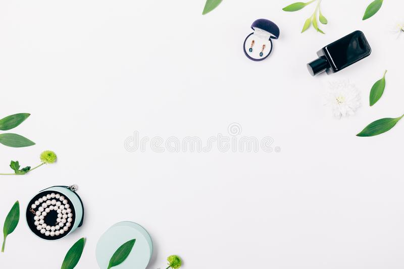 Feminine gifts jewelry and perfume among floral composition royalty free stock photos