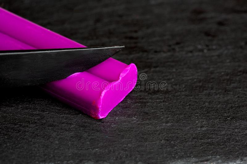 A feminine hand slices a purple clay stack on a black stone background. stock image