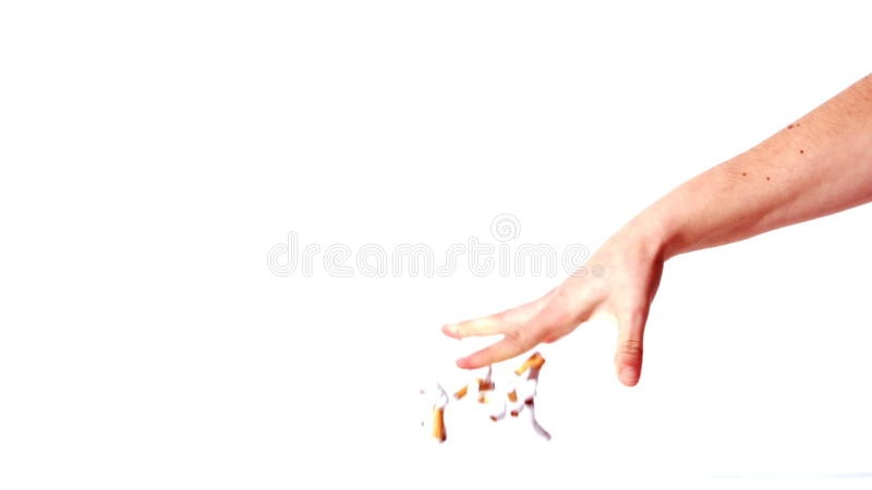 Feminine hand throwing a bung of crushed cigarettes on the floor. On white background stock video
