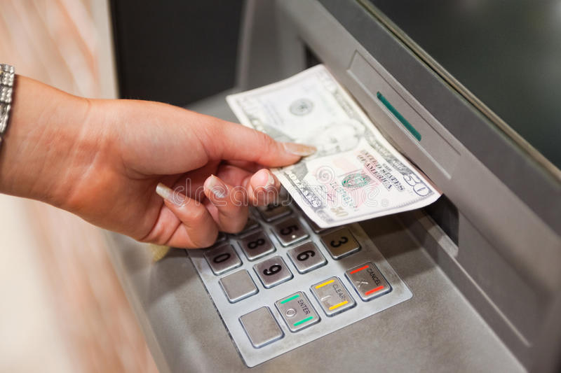 Feminine hand withdrawing dollars. At an ATM royalty free stock photos
