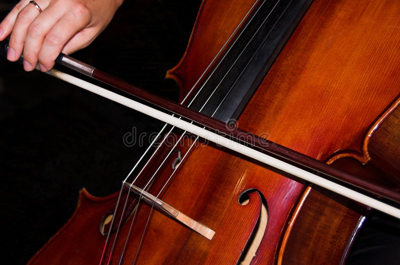 Feminine hands playing cello royalty free stock image
