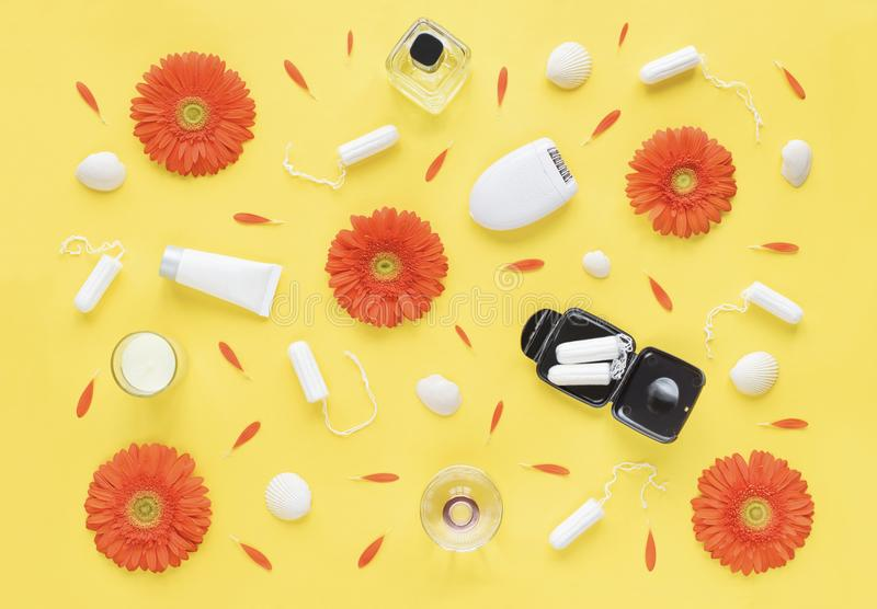 Feminine intimate hygiene set over yellow background with orange flowers and petals. Menstruation sanitary soft cotton tampons. Wo stock photos