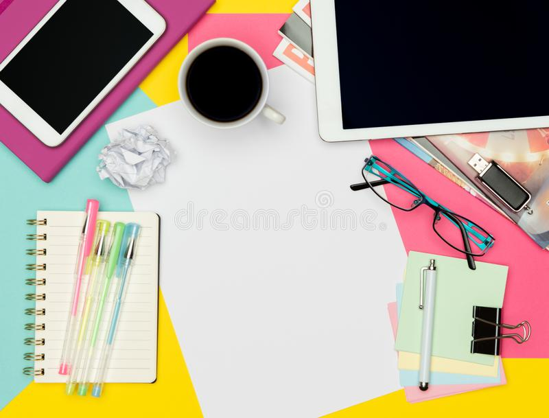 Feminine Office Desk Working Space Flat Lay. Top view photo of workspace with blank sheet of paper mock up and fashion magazines. stock photo