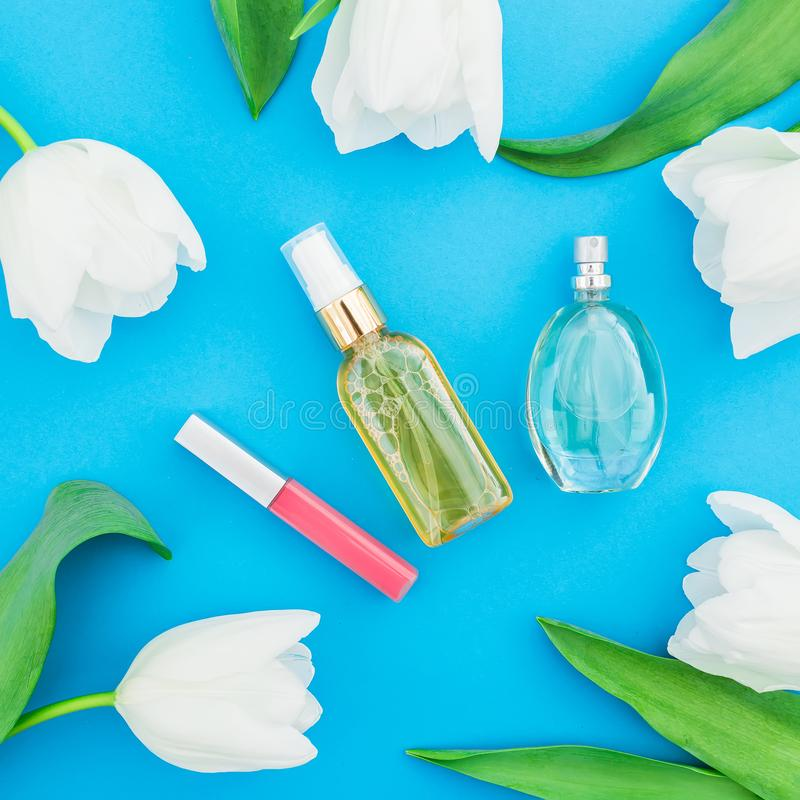 Feminine perfume, cream, lipstick and white tulips flowers on blue background. Beauty blog. Flat lay, top view stock image