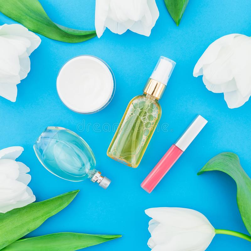 Feminine perfume, lipstick, cream and white tulips flowers on blue background. Beauty blogger. Flat lay, top view royalty free stock photo