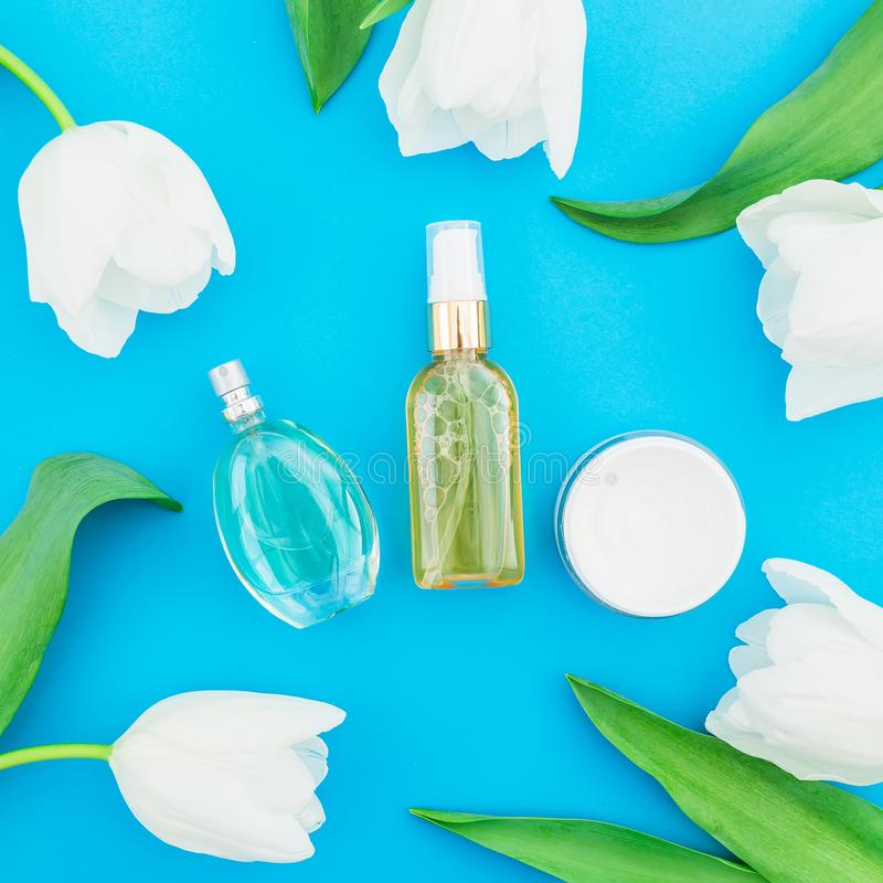 Feminine perfume, pink lipstick and white tulips flowers on blue background. Beauty blog royalty free stock photography