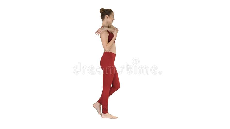 Feminine sportswoman stretching her arms during walk on white background. stock image