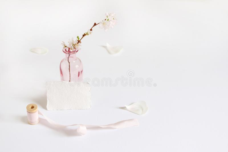 Feminine spring stationery mockup scene with a handmade paper greeting card, spool of silk ribbon and cherry blossoms in royalty free stock photo