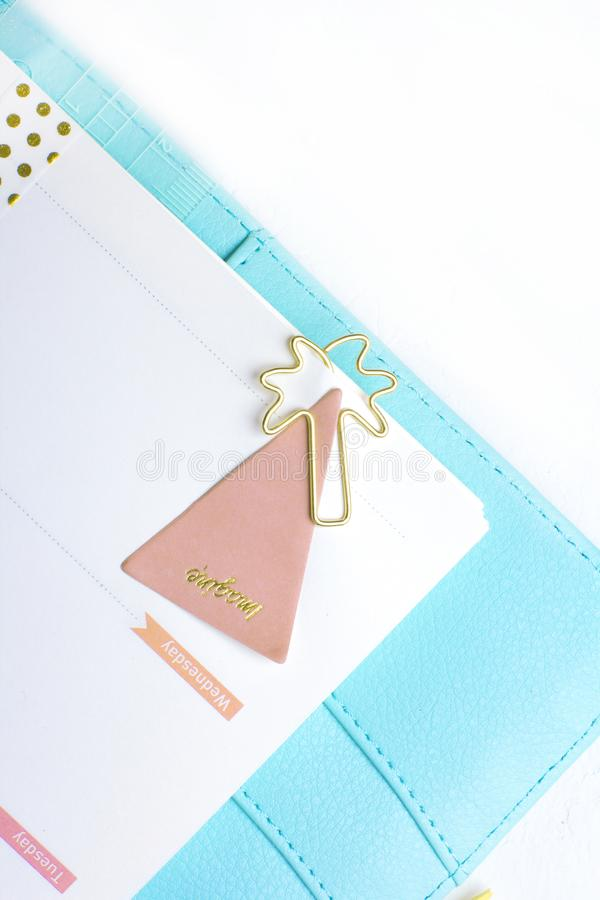 Feminine stationery: colorful paper binder clips palm and flamin. Go shape on white table background with washi tape. Flat lay style stock photo