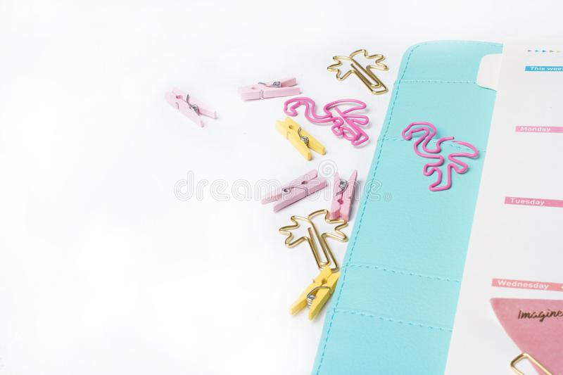 Feminine stationery: colorful paper binder clips palm and flamin. Go shape on white table background with washi tape. Flat lay style royalty free stock photos
