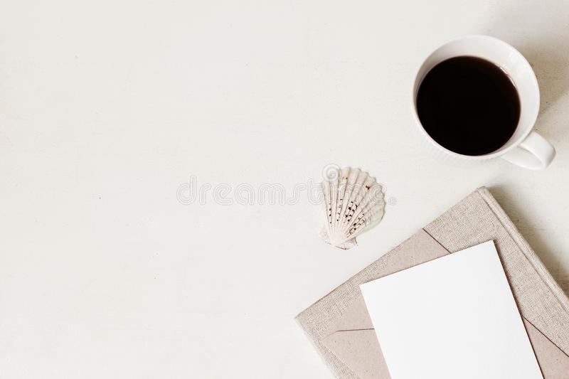 Feminine stationery, desktop mock-up scene. Blank greeting card, craft envelope, cup of coffee, sea shell and old books royalty free stock photo