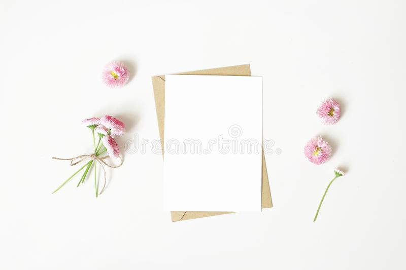 Feminine stationery, desktop mock-up scene. Vertical blank greeting card, craft paper envelope and daisy bouquet and royalty free stock photo